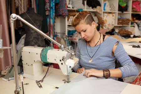 Young female blonde dressmaker cloth designer works on sewing machine. In her workspace. dress manufacturing industry. 版權商用圖片