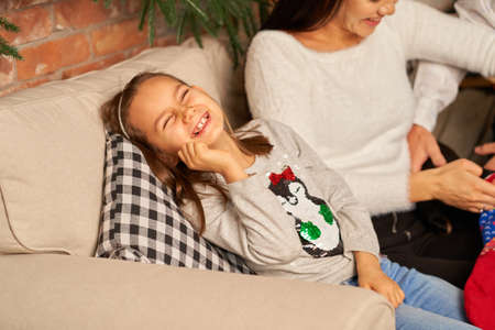 Little girl laughs having fun while spending time with parents at home on the couch.