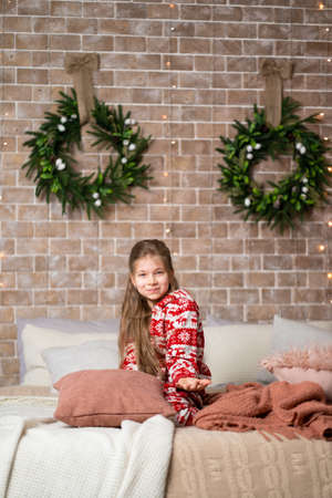Little girl in red pajamas on the bed in a cozy Christmas interior. Archivio Fotografico