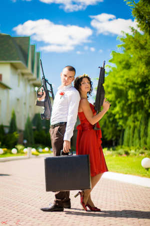 Young couple of criminals with weapons and a suitcase full of money.