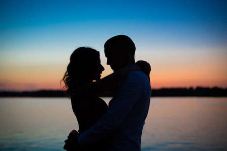 Silhouettes of a couple in love romance at sunset.