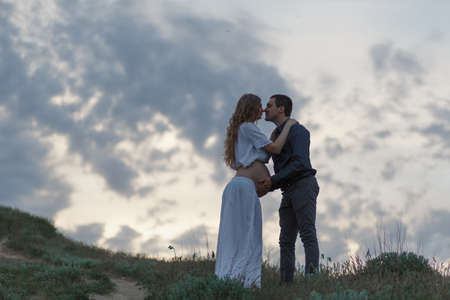 A couple in love, a pregnant wife in a white outfit are walking in a hilly field. Overcast weather,