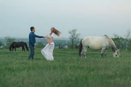 Rural couple on a green meadow communicates with animals. Pregnant wife. Therapy and relaxation for pregnant women. Banque d'images