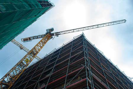 Construction site jib crane. Construction of new modern buildings. Urban architecture.