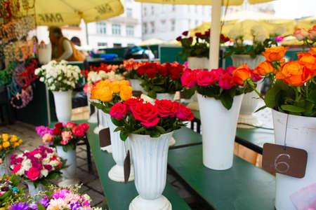 Street flower shop. Flowers in vases on the street.
