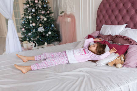 The little girl doesn't want to go to bed on Christmas night. Christmas tale. Magic moments of happy childhood.