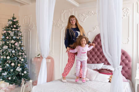 Happy little girl in pajamas is jumping with mom on the bed. Christmas tale. Happy childhood.