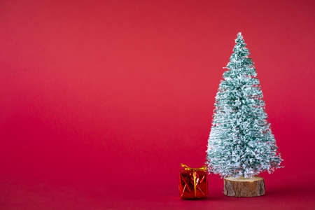 Christmas holiday background. Snow-covered Christmas tree and bright multi-colored boxes with gifts. Copy space.