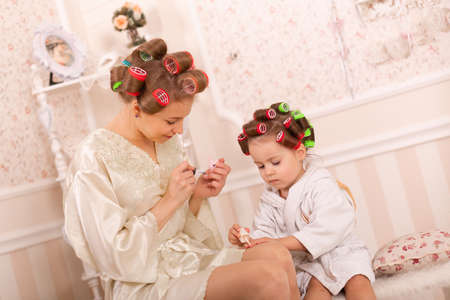 Adorable little girl with her mother in curlers paint their fingernails. Copies mom's behavior. Mom teaches her daughter to take care of herself. Beauty day.