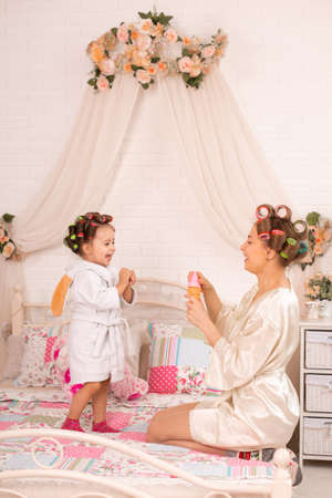 A charming little girl with her mother in hair curlers play with soap balls. Women's day. The girl has fun with her mom.