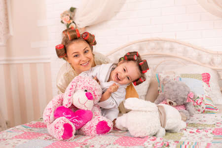 A charming little girl with her mother in hair curlers are having fun. Women's Day. Girl having fun with mom. Reklamní fotografie