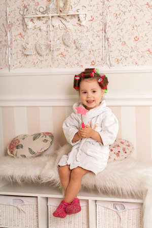 Charming little girl with curls hair using curlers. Copies mom's behavior. Young fashionista.