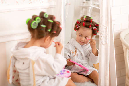 Adorable little girl learns to use baby cosmetics. Beauty day. Reklamní fotografie