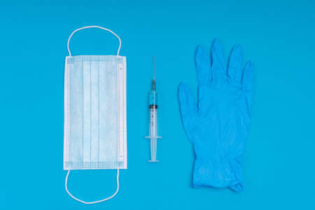 Popular medical antiviral mask, a syringe with a virus vaccine and medical gloves on a blue background.