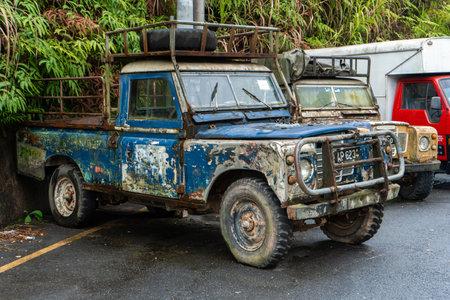 Two old rusty peeled paint farm trucks in an Asian village. Redakční