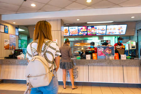 Queue at the cash desk of a fast food restaurant. Masked cashier. People in line keep their distance. Coronavirus pandemic.