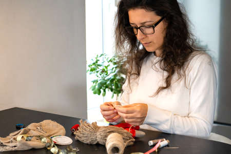 Handicraft is a fascinating hobby. The person sews dolls at their leisure. Reklamní fotografie