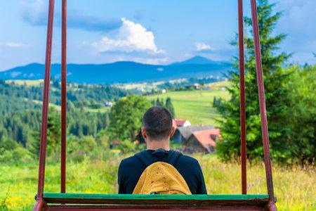 The guy tourist sit on the swing and enjoy amzing nature landscape of summer Karpaty mountains. Reklamní fotografie