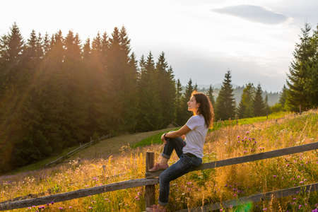 The girl enjoy sunset sitting on wooden fence on highlands field next to forest.