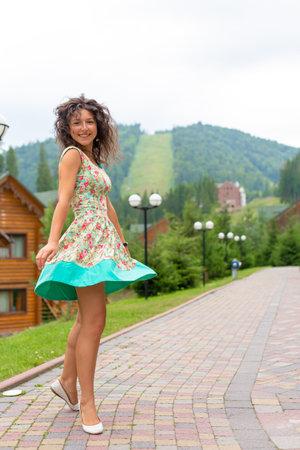 A beautiful slim girl posing next to mountain ski resort in the summer day.
