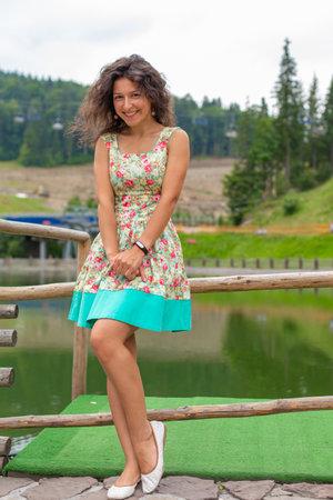 A beautiful slim girl posing in green summer park next to pond. Reklamní fotografie