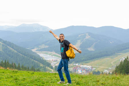 A guy travels with a yellow backpack through picturesque places with beautiful mountain landscapes.