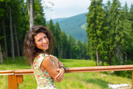 Happy gorgeous girl enjoy mountain view stay in summer dress on the hill with breathtaking mountain landscape.