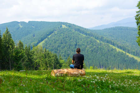 Guy sitting on log and enjoy peaceful green mountains landscape. Peace of mind and relax.