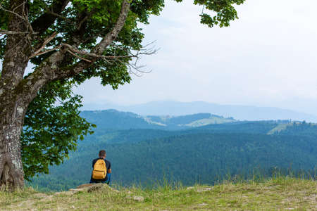 Alone guy sitting on cliff and enjoy peaceful green mountains landscape. Peace of mind and relax. Reklamní fotografie