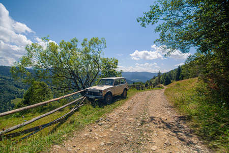Old russian jeep parked next to wooden fence on the mountain dirty road. Summer day. Mountain tour. Redakční