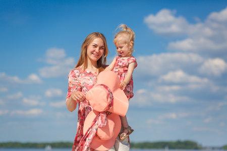 一个迷人的女孩在一个轻的夏天sundress走在与她的小女儿的沙滩。享受温暖的阳光灿烂的夏日。