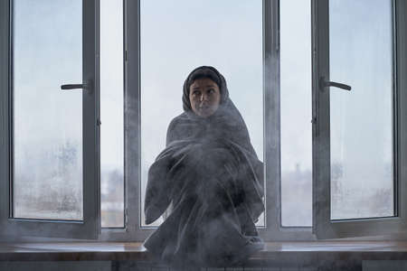 Cold winter weather. A woman is shaking from the cold sitting on the windowsill, wrapped in a blanket. Frosty air rushes in from the open window. Airing housing in cold winter.