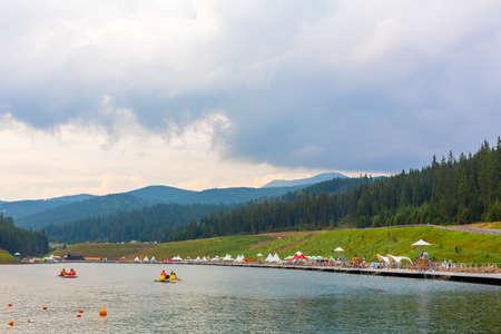 Entertaiment of Voda club on the pond among Carpathian mountains. Rental boats for lake tour.