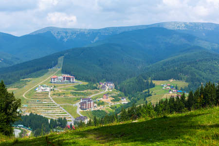 Mountain ski slope in summer day. Green mountains landscape on background.
