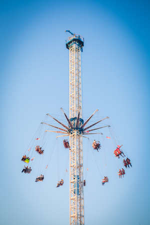 People have fun enjoying the air carousel in the amusement park.