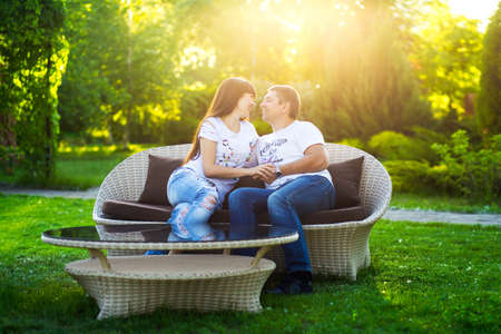Young romantic couple have fun enjoy each other on the bench in green summer park. Editorial