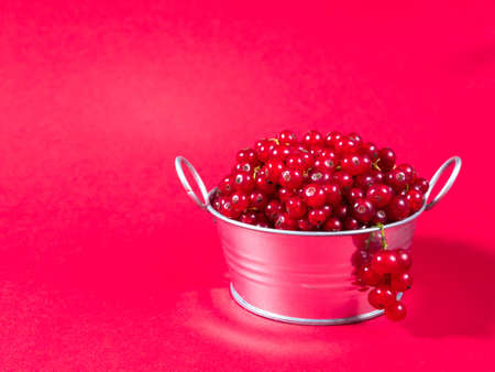 A metal basin filled with red currants on pink background.