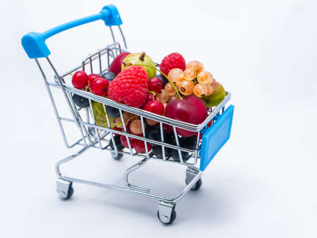 Mini grocery cart filled with fresh vitamin berries isolated on white background.