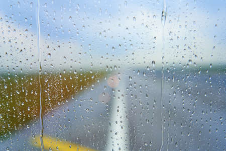 View through the foggy glass of an airplane before takeoff on a rainy day. Foto de archivo