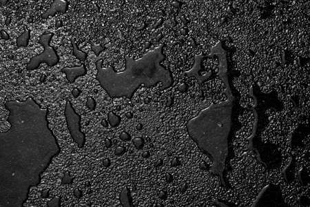 Water is spilled on a black textured surface.