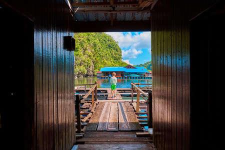 A little boy walks on a wooden pier on a floating fish farm.