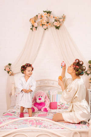 A charming little girl with her mother in hair curlers play with soap balls. Women's day. The girl has fun with her mom. Foto de archivo