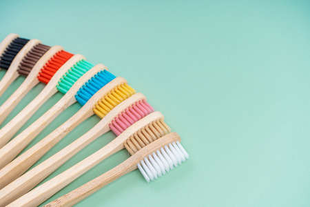 A set of Eco-friendly antibacterial toothbrushes made of bamboo wood on a light green background. Environmental care trends. 写真素材