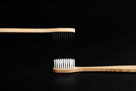 Two Eco-friendly antibacterial bamboo wood toothbrushes with white and black bristles on a black background. Taking care of the environment is trending. Tolerance. Copy space.