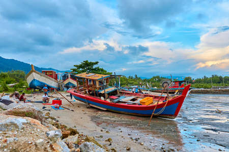 Old boat on the sandy river bank in the fishing village. Fishing village on an island in Asia. 報道画像