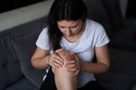 Close-up of a person massaging an injured knee joint. Bruise on the knee. Leg pain.