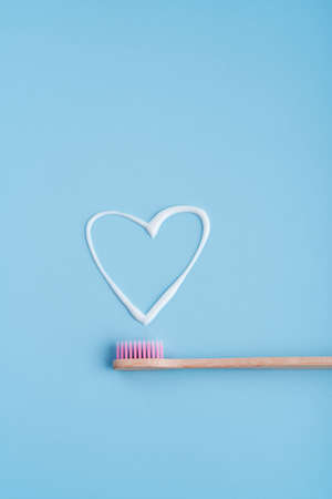 Eco-friendly trendy bamboo toothbrush. Popular toothbrushes. Hygiene trends. Top view with toothpaste.