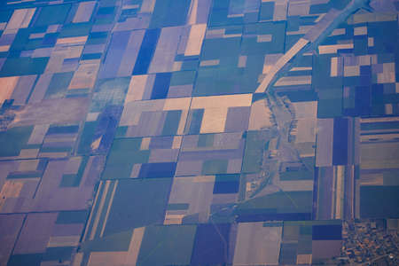 Daytime view from a flying plane over fields and land shares.