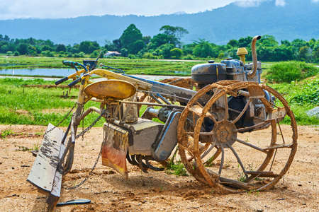 A strange homemade tool for plowing a field from a rebuilt motorbike. Agricultural village in Asia.