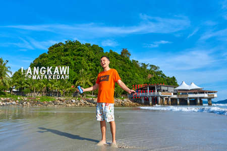 happy tourist guy on the central beach in Langkawi tropical island. Langkawi, Malaysia - 06.20. 新闻类图片